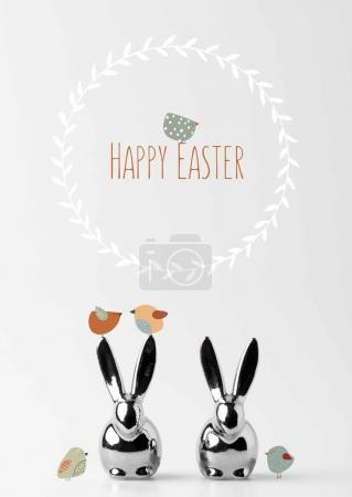 Photo for Two statuettes of easter bunnies with drawn birds and happy easter lettering on white - Royalty Free Image