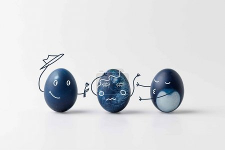 three blue painted easter eggs with comic drawn faces on white surface