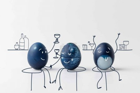 three blue painted easter eggs with drawn faces drinking at bar on white surface