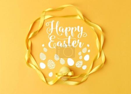 Photo for Top view of yellow painted easter egg with ribbons on yellow with happy easter lettering - Royalty Free Image