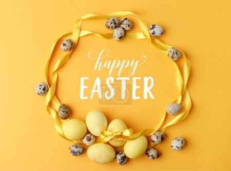 Photo for Top view of yellow painted easter eggs and quail eggs on yellow with happy easter lettering - Royalty Free Image