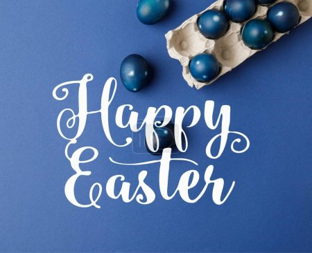 top view of blue painted easter eggs and egg tray with happy easter lettering on blue surface