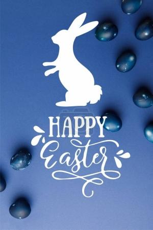top view of blue painted easter eggs with happy easter lettering and rabbit silhouette on blue surface