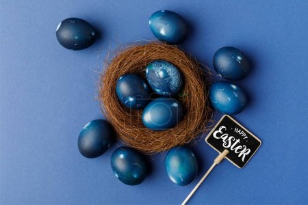 top view of blue painted easter eggs in decorative nest and happy easter lettering on signboard on blue surface