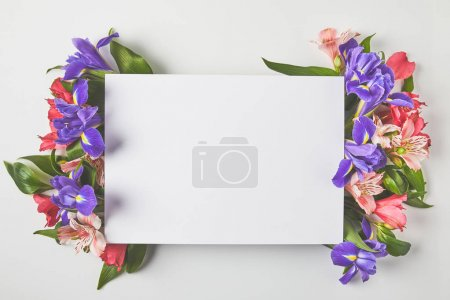top view of blank card and beautiful tender flowers on grey