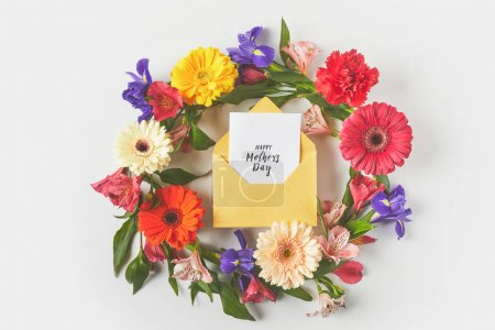 top view of beautiful floral wreath and happy mothers day greeting card in envelope on grey