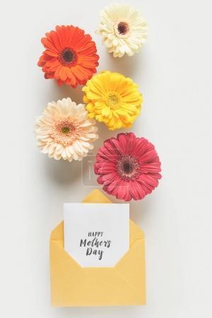 Photo pour Vue du dessus de belles fleurs de gerbera tendres et enveloppe avec carte de vœux joyeuse fête des mères sur gris - image libre de droit