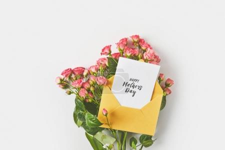 happy mothers day greeting card in envelope and beautiful pink roses on grey