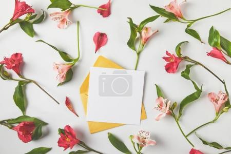 Photo for Top view of blank card with envelope and beautiful pink flowers with green leaves on grey - Royalty Free Image