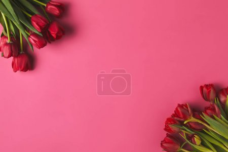 top view of red tulips bouquets on pink, mothers day concept