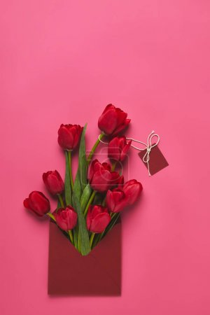 top view of red tulips in envelope with blank tag on pink, mothers day concept