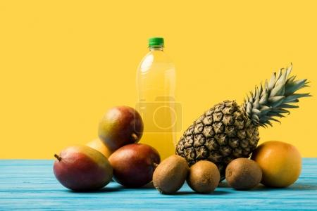 fresh ripe tropical fruits and natural fruity drink in plastic bottle on turquoise wooden table