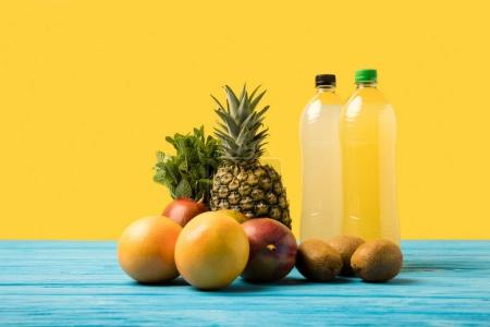 close-up view of fruity drinks in plastic bottles and fresh ripe tropical fruits on yellow