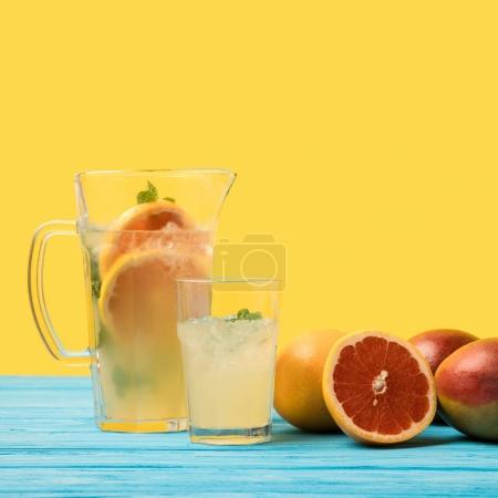 close-up view of fresh mangoes with grapefruits and cold summer drink in glass and jug on yellow