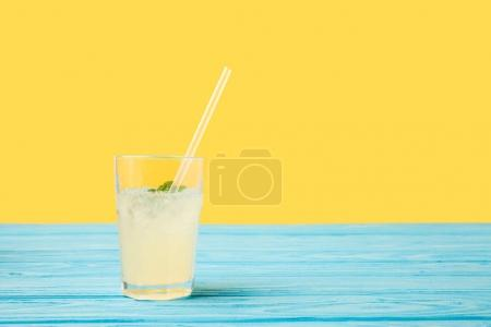 fresh cold summer drink in glass with drinking straw on turquoise wooden table top