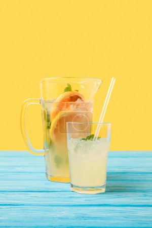 close-up view of fresh cold summer drink in glass and jug on yellow