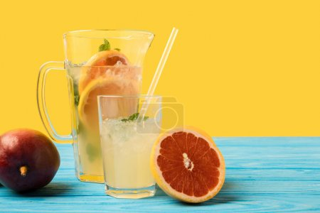 sliced grapefruit, ripe mango and fresh cold summer drink in glass and jug on turquoise wooden table