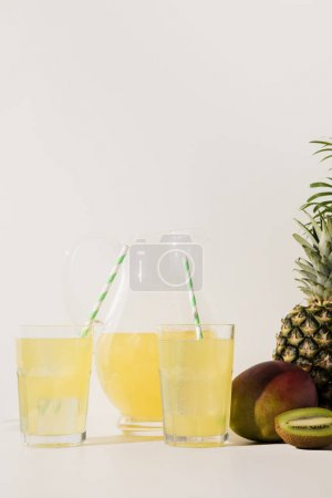 glasses with straws and glass jug with juice and fresh tropical fruits on grey