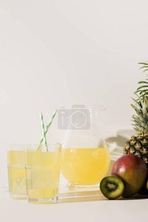 vue rapprochée des verres et verseuse en verre avec du jus et des fruits tropicaux frais sur fond gris