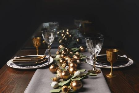 restaurant table with easter decoration and golden eggs
