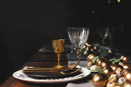 glasses, plates and easter eggs on festive table in restaurant