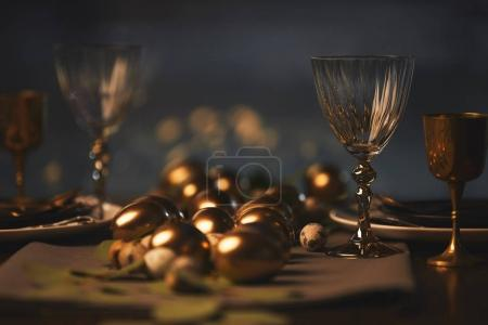 easter decorated table with golden chicken eggs