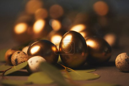 close up of easter golden eggs with leaves on table