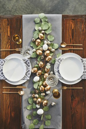 top view of easter golden eggs, plates and glasses on festive table in restaurant