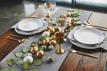 easter golden eggs, plates and glasses on table in restaurant