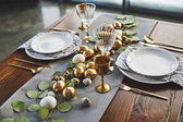 easter golden eggs, plates and glasses on table in restaurant
