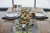 easter golden eggs, plates and glasses on table
