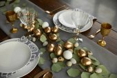 high angle view of golden chicken eggs and quail eggs on festive easter table