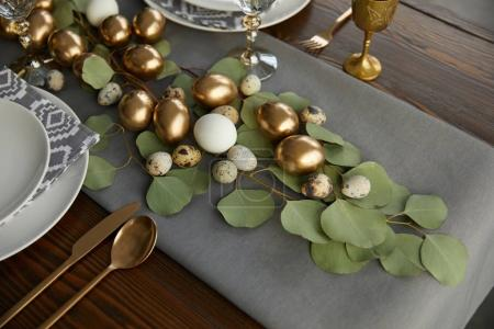 golden easter eggs on green leaves on festive table