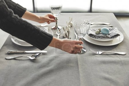 cropped image of waiter serving easter table in restaurant