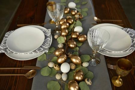 high angle view of golden easter eggs on wooden table in restaurant