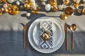 top view of golden egg and quail eggs on plates in restaurant, easter concept