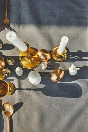 top view of candles and easter eggs on festive table