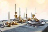 golden chicken eggs and candles on festive table