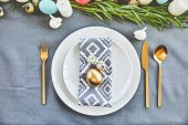 top view of golden easter egg and quail eggs on festive plates in restaurant