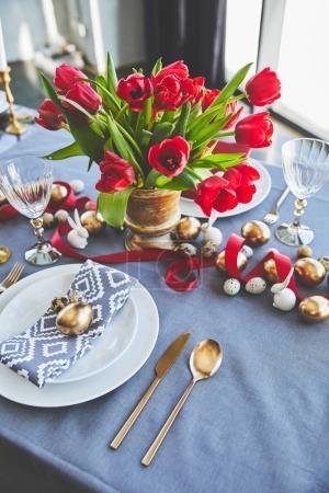 vista de ángulo alto de bouquet de tulipanes rojos y Pascua huevos en mesa festiva