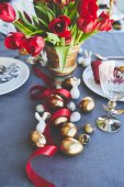 bouquet of red tulips and easter eggs on festive table