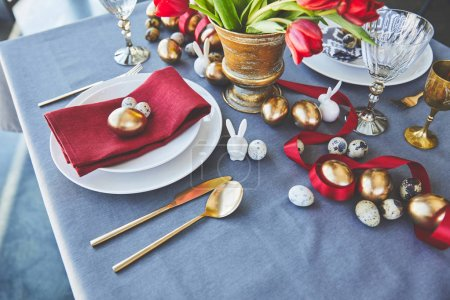 high angle view of easter golden eggs and flowers on festive table in restaurant