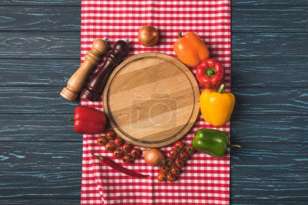 top view of ripe organic vegetables and pepper grinders around wooden board on table