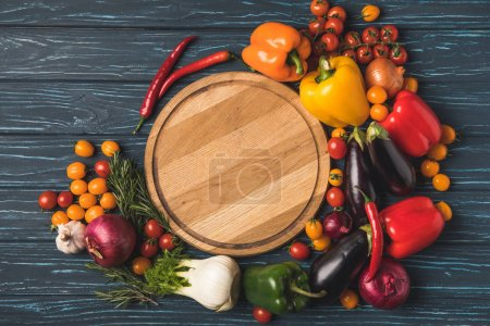 Photo for Top view of ripe organic vegetables around cutting board on wooden table - Royalty Free Image
