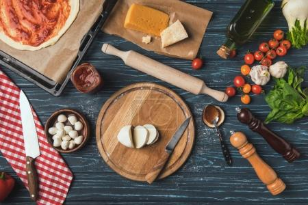 top view of ingredients for homemade pizza on kitchen table