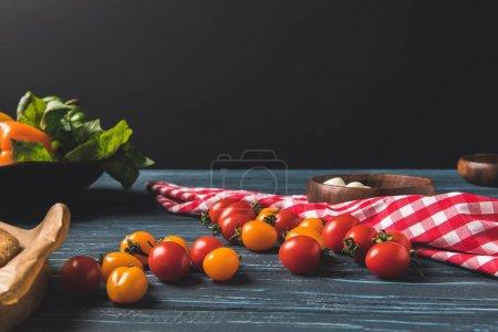 Photo pour Tomates cerises et la nappe sur la table en bois - image libre de droit