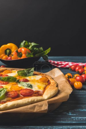 Photo for Close up of appetizing homemade pizza with cherry tomatoes and basil - Royalty Free Image