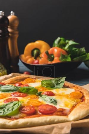Photo for Close up of appetizing tasty pizza with cherry tomatoes and basil - Royalty Free Image