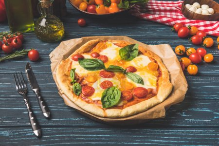 Photo for Appetizing tasty pizza with cherry tomatoes and basil on table - Royalty Free Image