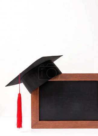 Photo for Empty blackboard with square academic cup isoalated on white - Royalty Free Image